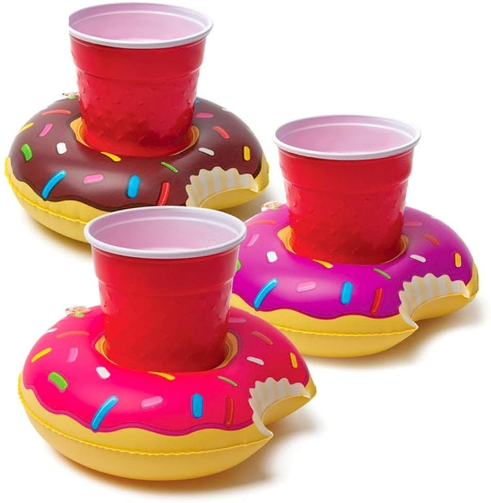 Three of the floaties, which are shaped like donuts with bites taken out of them, holding red plastic cups