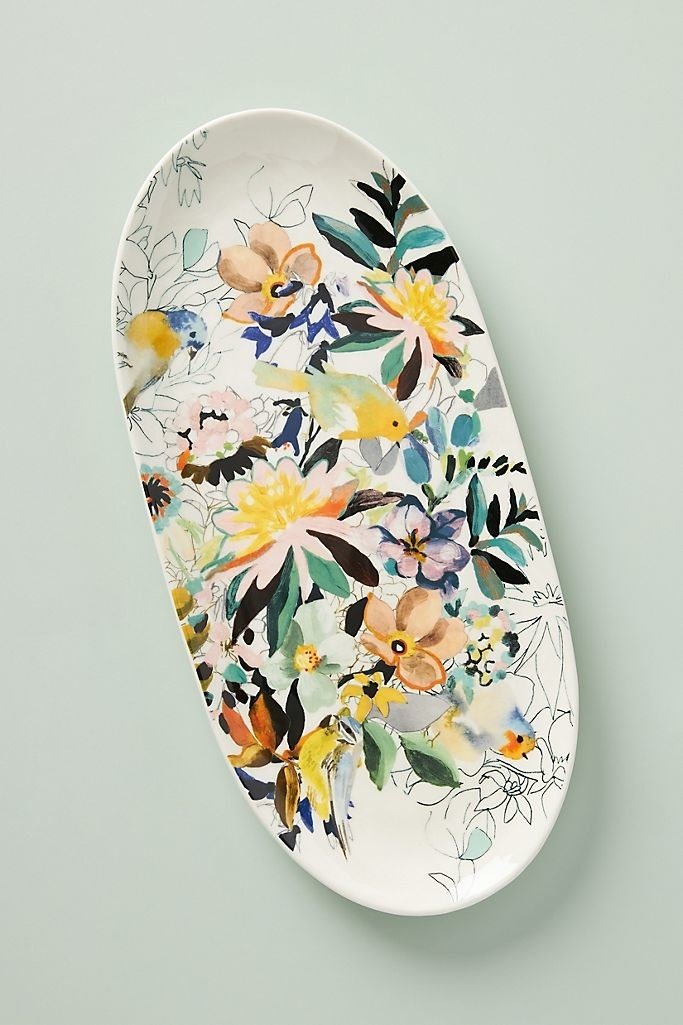 The oval platter in white  with multicolored flowers painted on it.