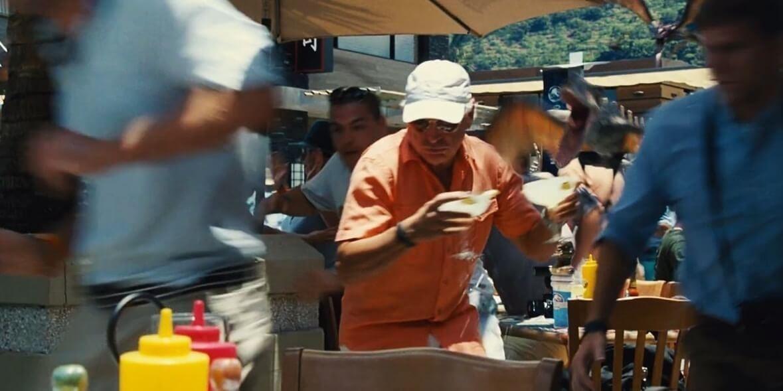 Jimmy Buffett running with margaritas in each hand