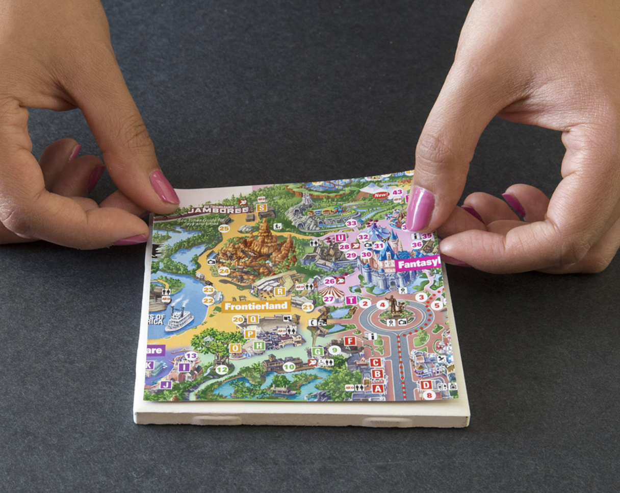 Hands place a cut piece of a Disney map onto a coaster.