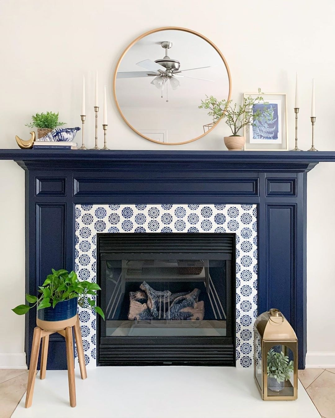 A fireplace's mantle is painted navy blue to contrast the off-white walls
