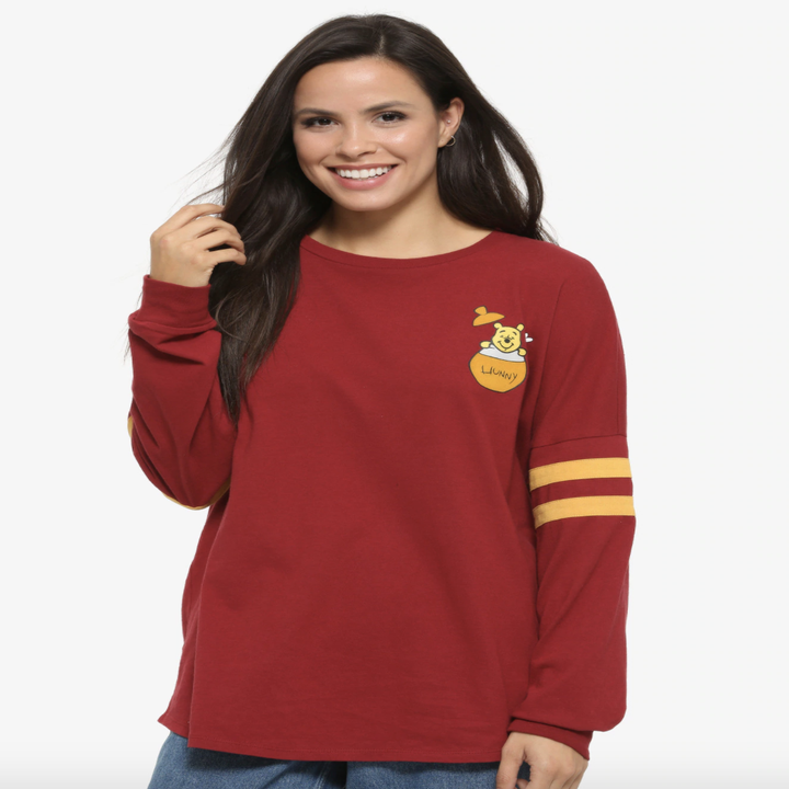 "a model in a darker red long sleeve with two yellow stripes on the sleeves and winnie the pooh sitting in a ""hunny"" pot on the top right corner"