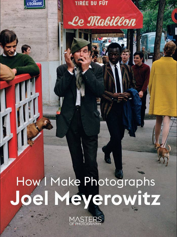 """The book cover for """"How I Make Photographs"""" by Joel Meyerowitz shows a man playing a harmonica and smoking a cigarette on the sidewalk while other pedestrians stare at him"""