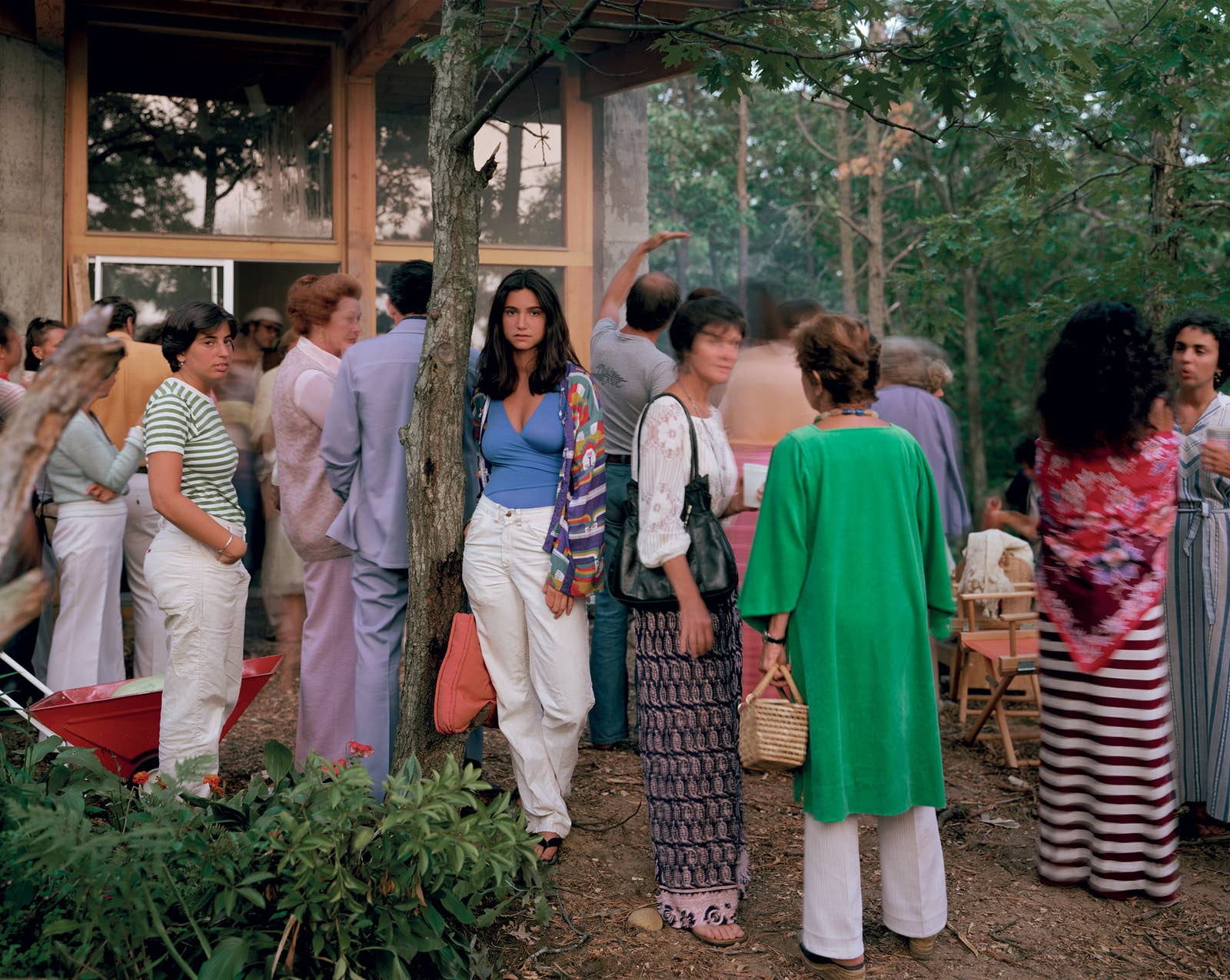 A young woman stands next to a tree and stares into the camera while surrounded by people at a crowded function