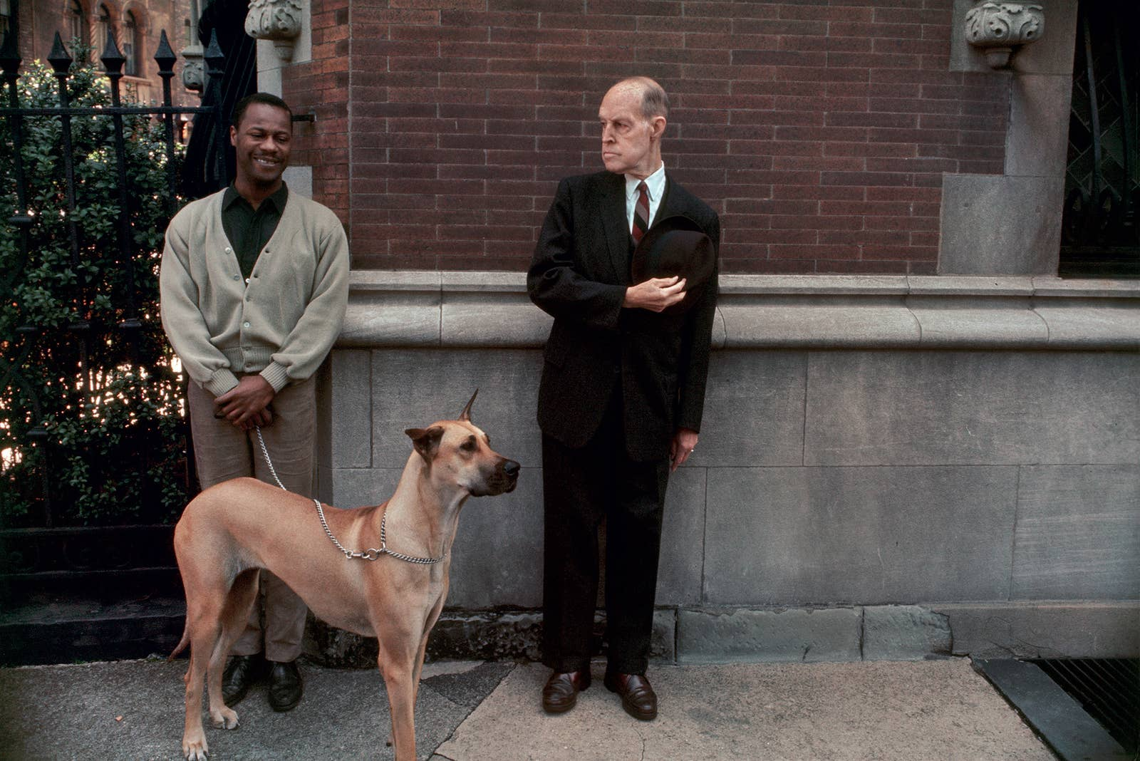 A man looks on at a second man holding a dog on a chain leash