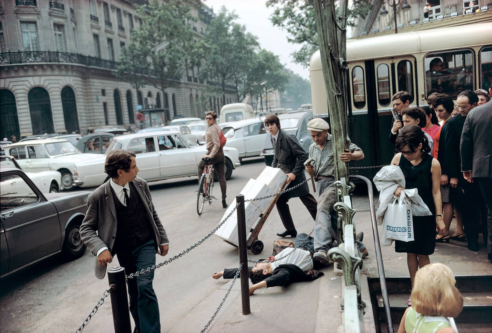 A man lies on the ground in the middle of a crowded city street while a cyclist and pedestrians look at him