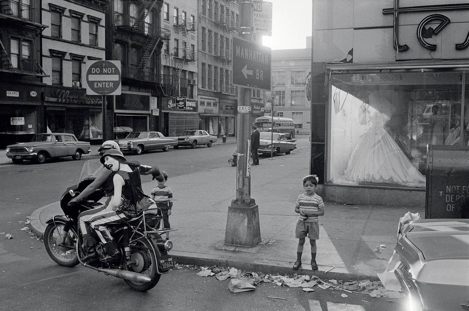 Two boys standing on the sidewalk watch a motorcycle drive by