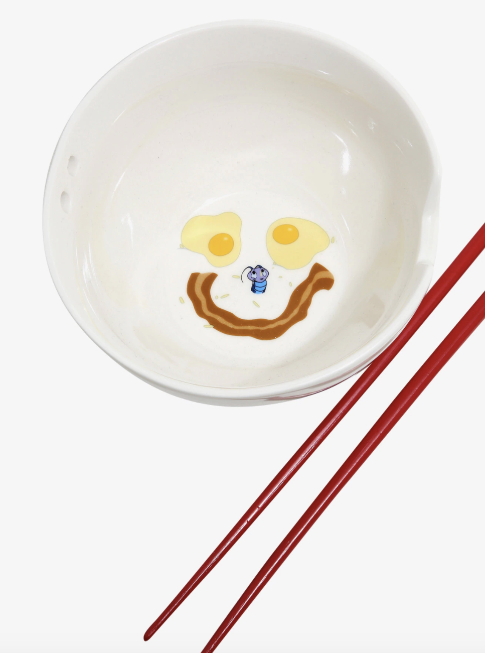 a bowl with the eggs and smile made of bacon drawn on the inside in addition to kri-kee from the movie mulan alongside red chopsticks