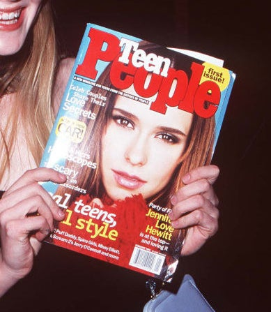 A cropped photo of Kirsten Dunst holding up a Teen People with Jennifer Love Hewitt on the cover.