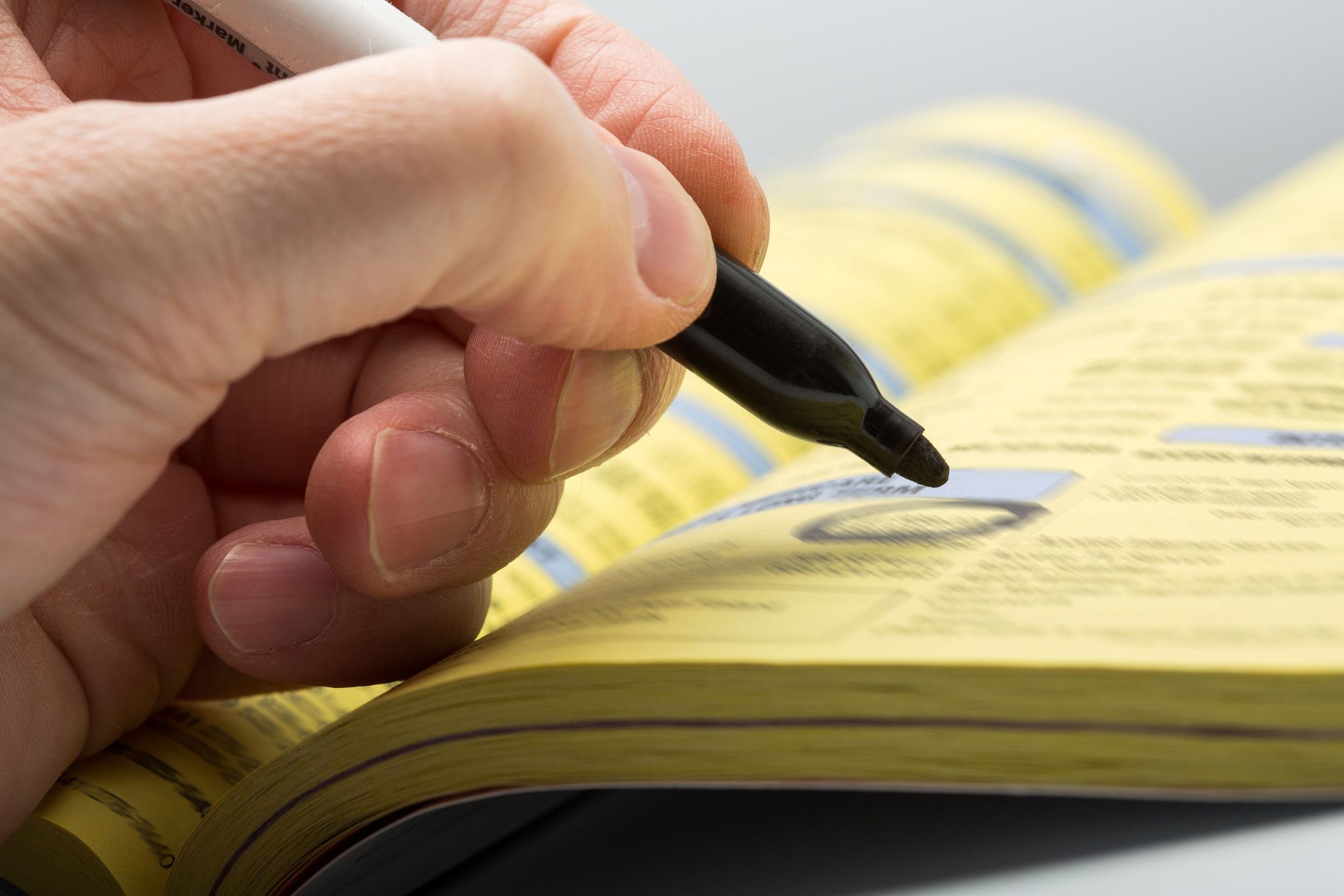 A stock photo of a someone circling a number in the phone book with a black marker.
