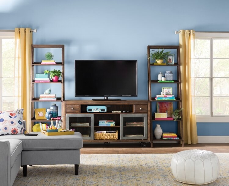 A living room with a TV on an entertainment stand, bookended by two shelves