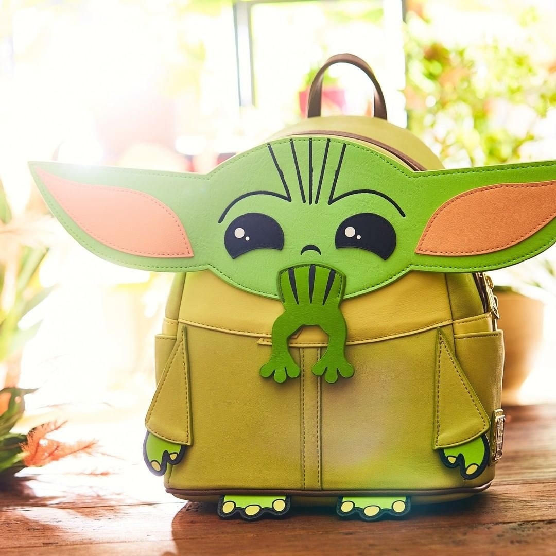 a tan and green backpack of baby yoda eating a frog
