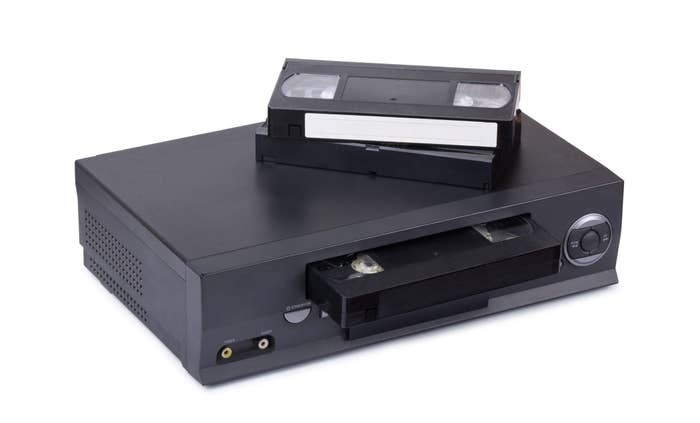 A stock image of a VCR with two VHS tapes on the top of it.