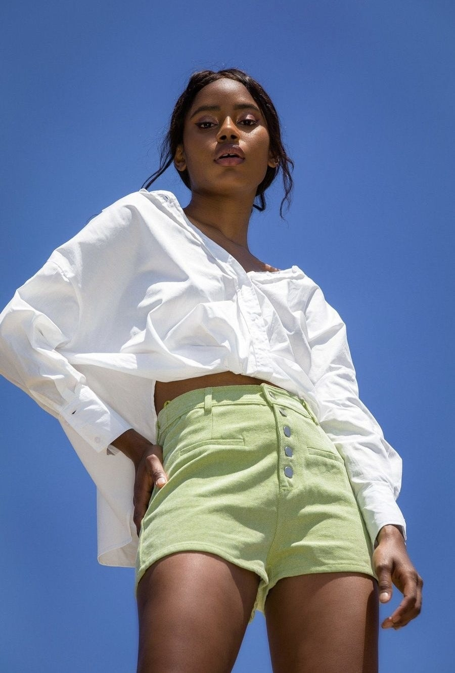 Model wearing the shorts with silver buttons down the front in lime green