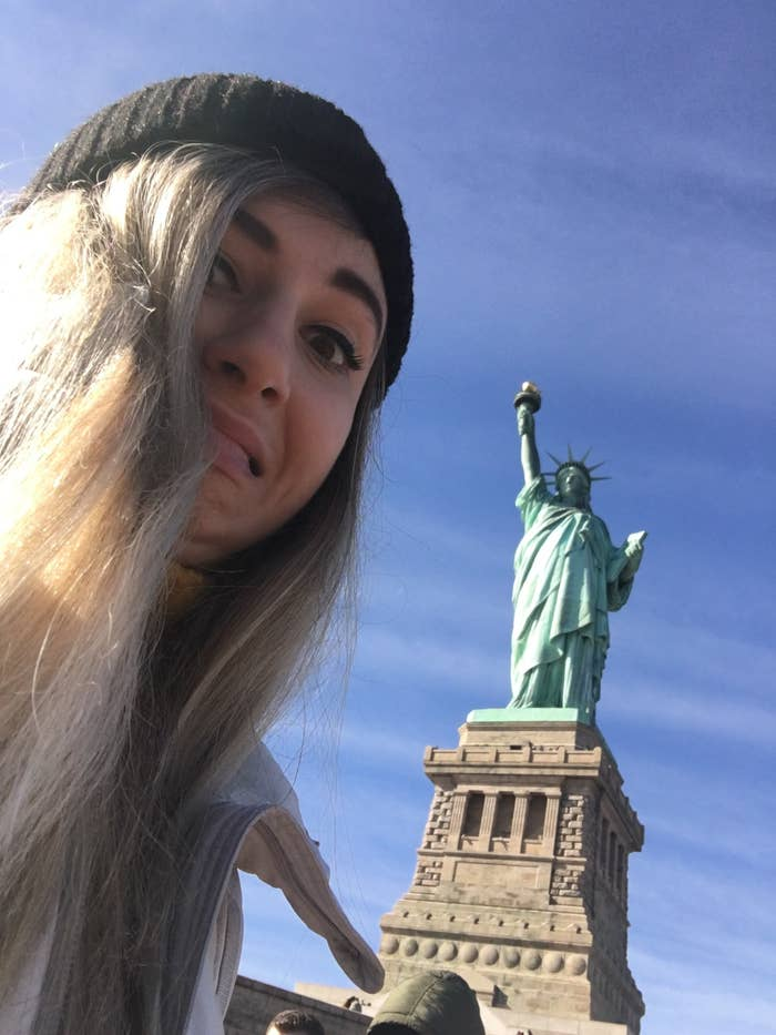 The writer pulling a hideous facial expression by the Statue of Liberty