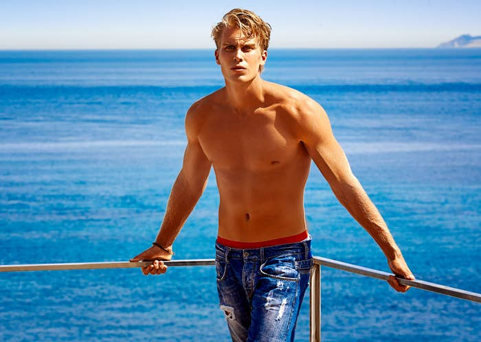 handsome shirtless blonde guy against a beach backdrop