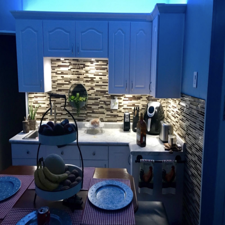 A kitchen with blue LED lights installed in the cabinets