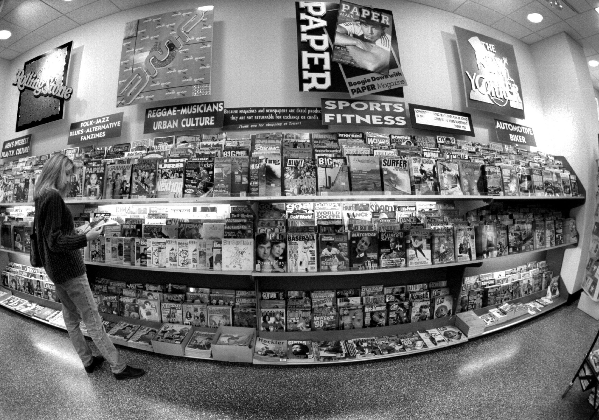 A fish-eyed lensed black and white photo of the magazine section at Tower Records in 1998.