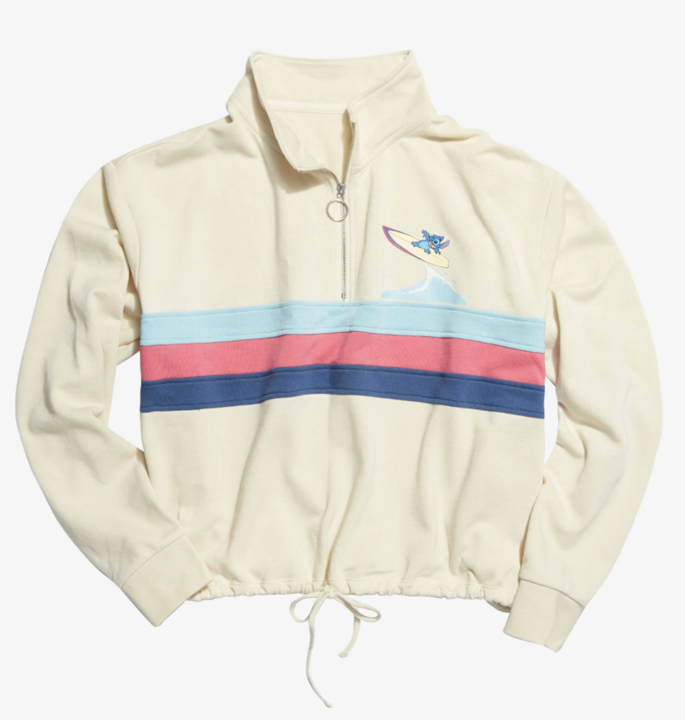 an off white half zip with three stripes in light blue, light red, and navy blue across it and stitch surfing a wave on the top right corner