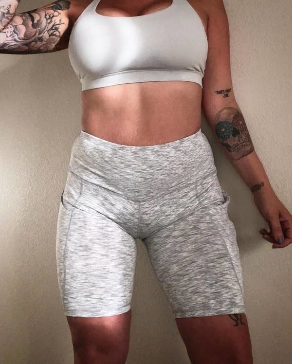 Reviewer wearing the shorts with pockets on either side and that go down the thigh in heather grey