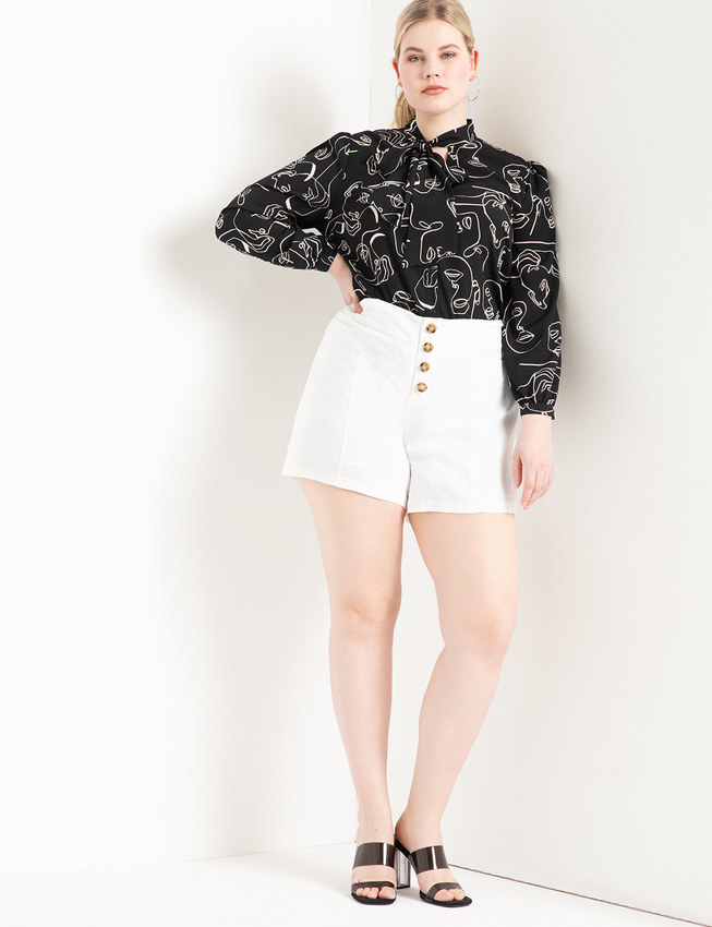 Model wearing the short with brown buttons down the front and a long-sleeved black and white blouse