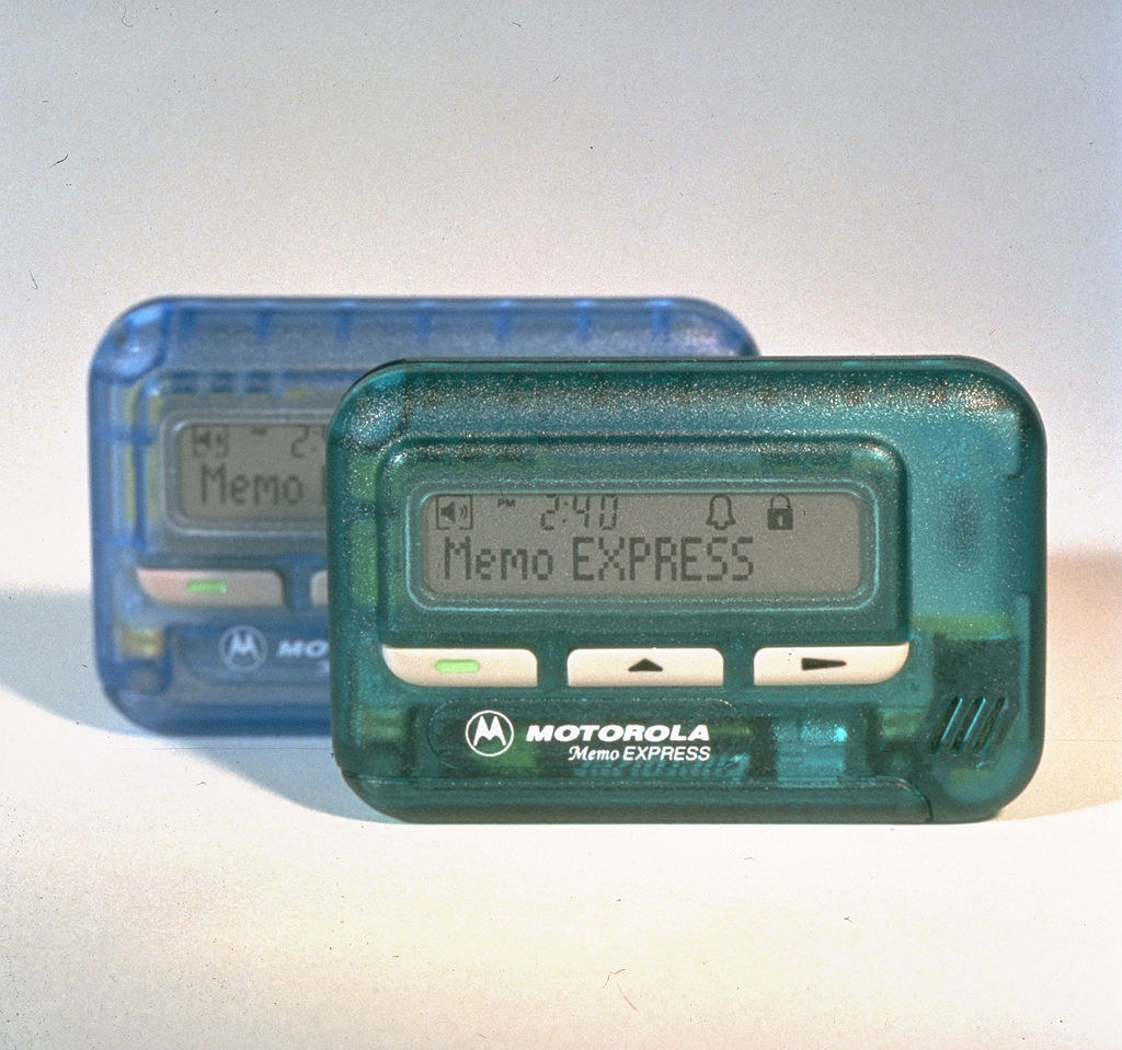 A photo of two Motorola pagers, one in baby blue and one in sea green.