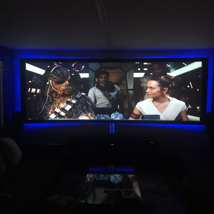 A tv playing star wars backlit with blue light