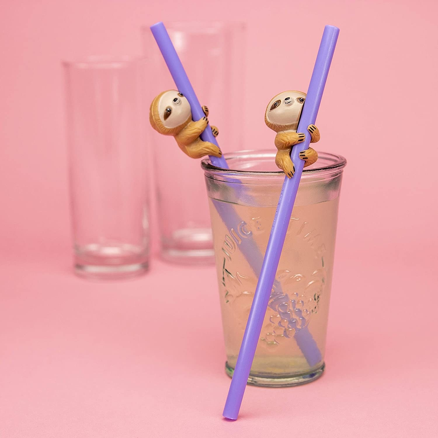 The purple straws with sloth figurines gripping the sides. One is in a glass of water and the sloth is just above the rim of the glass