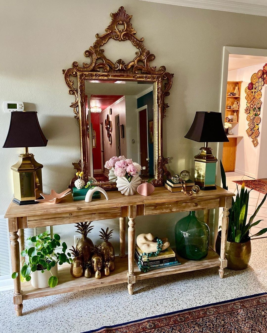 A large, ornate mirror sits on a console table as a focal point