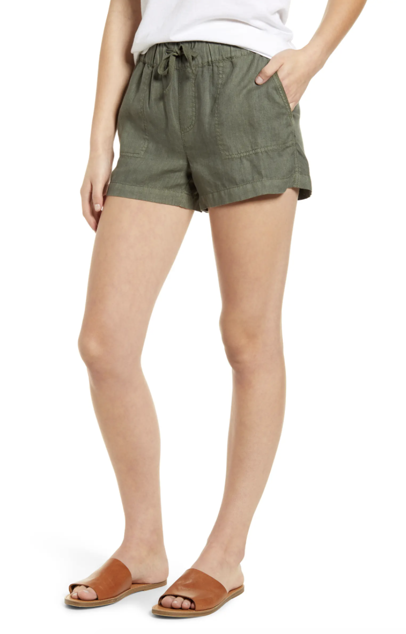 Model wearing the shorts with elastic tie waist and pockets in olive green