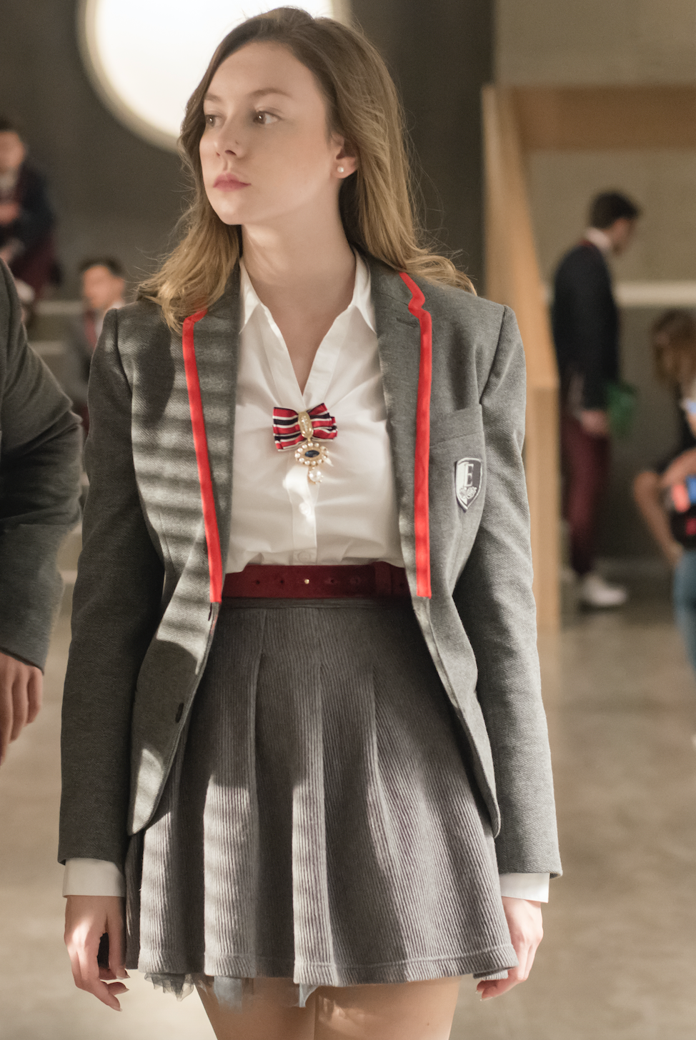 Carla accessorizing her school uniform with a brooch and belt