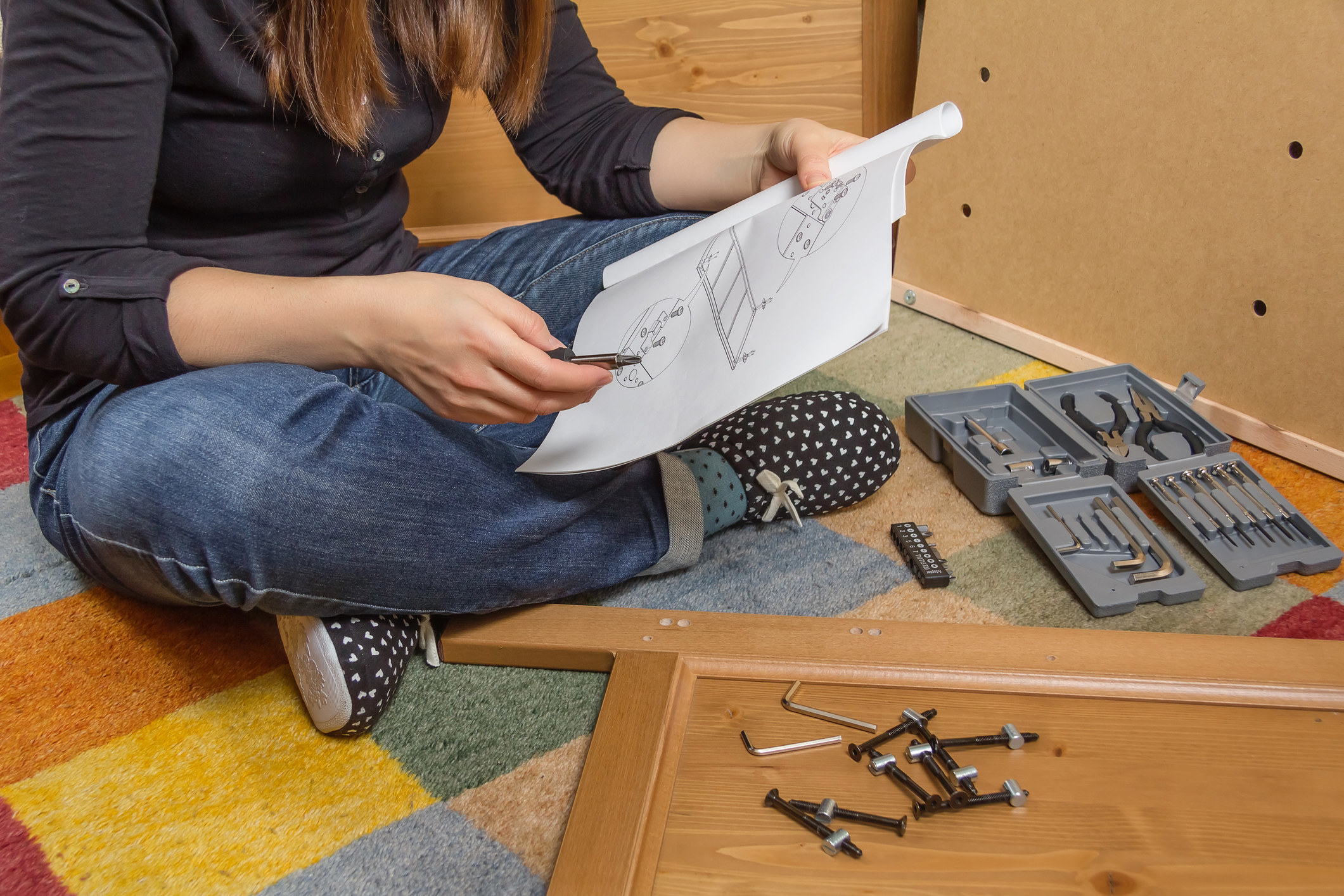 Woman assembling a piece of furniture reading the instruction manual