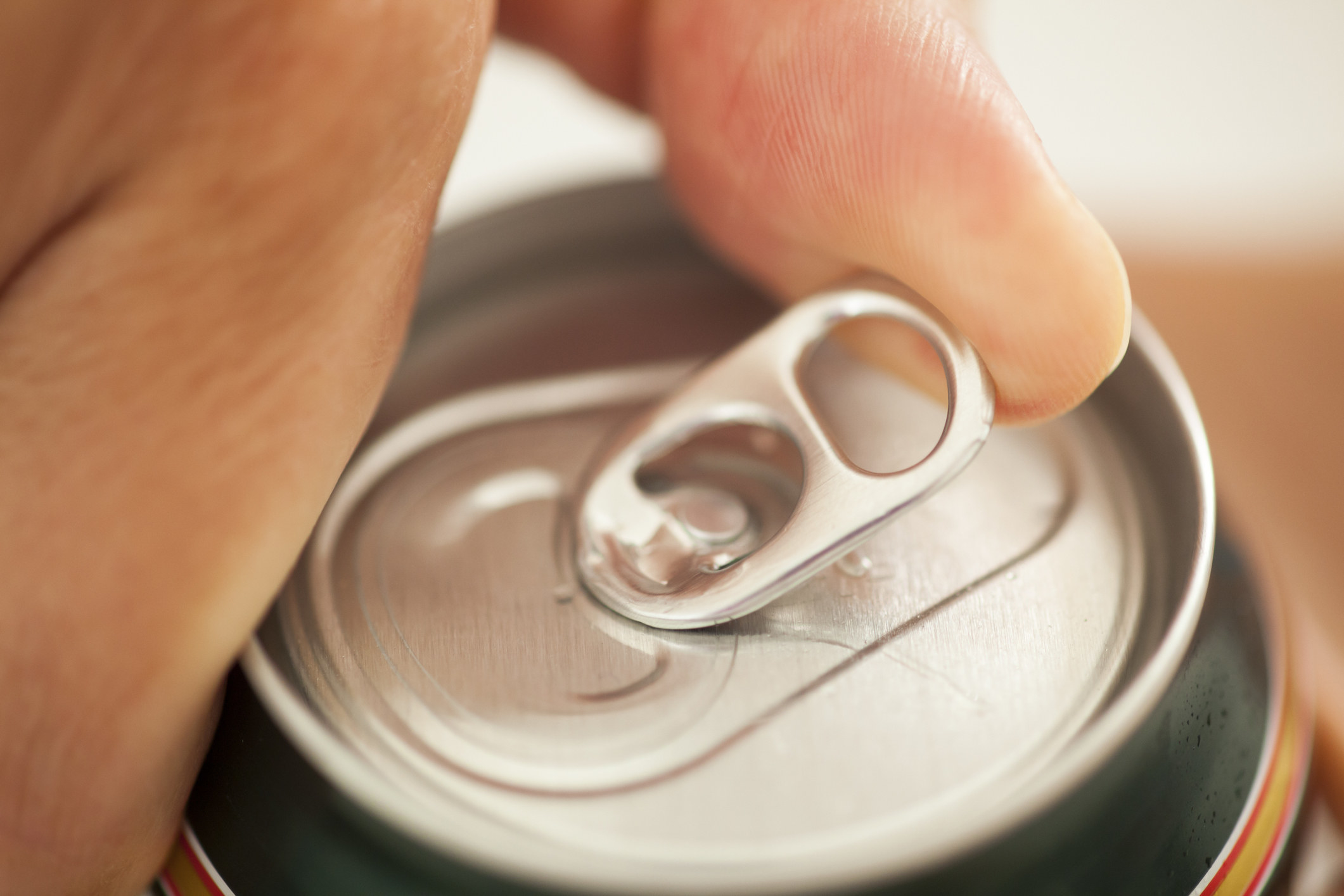 A hand opening a can of soda