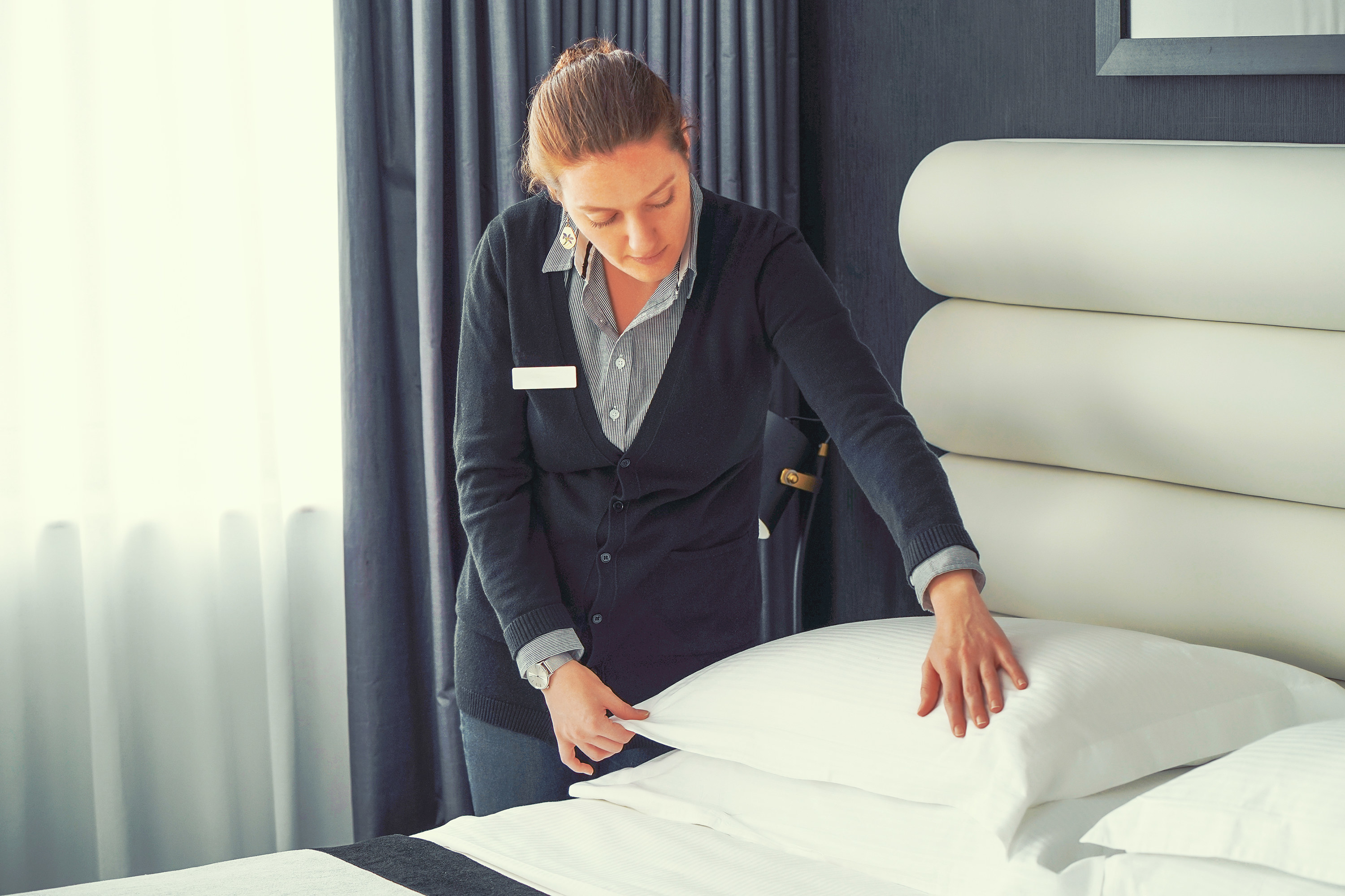 Hotel employee making a bed