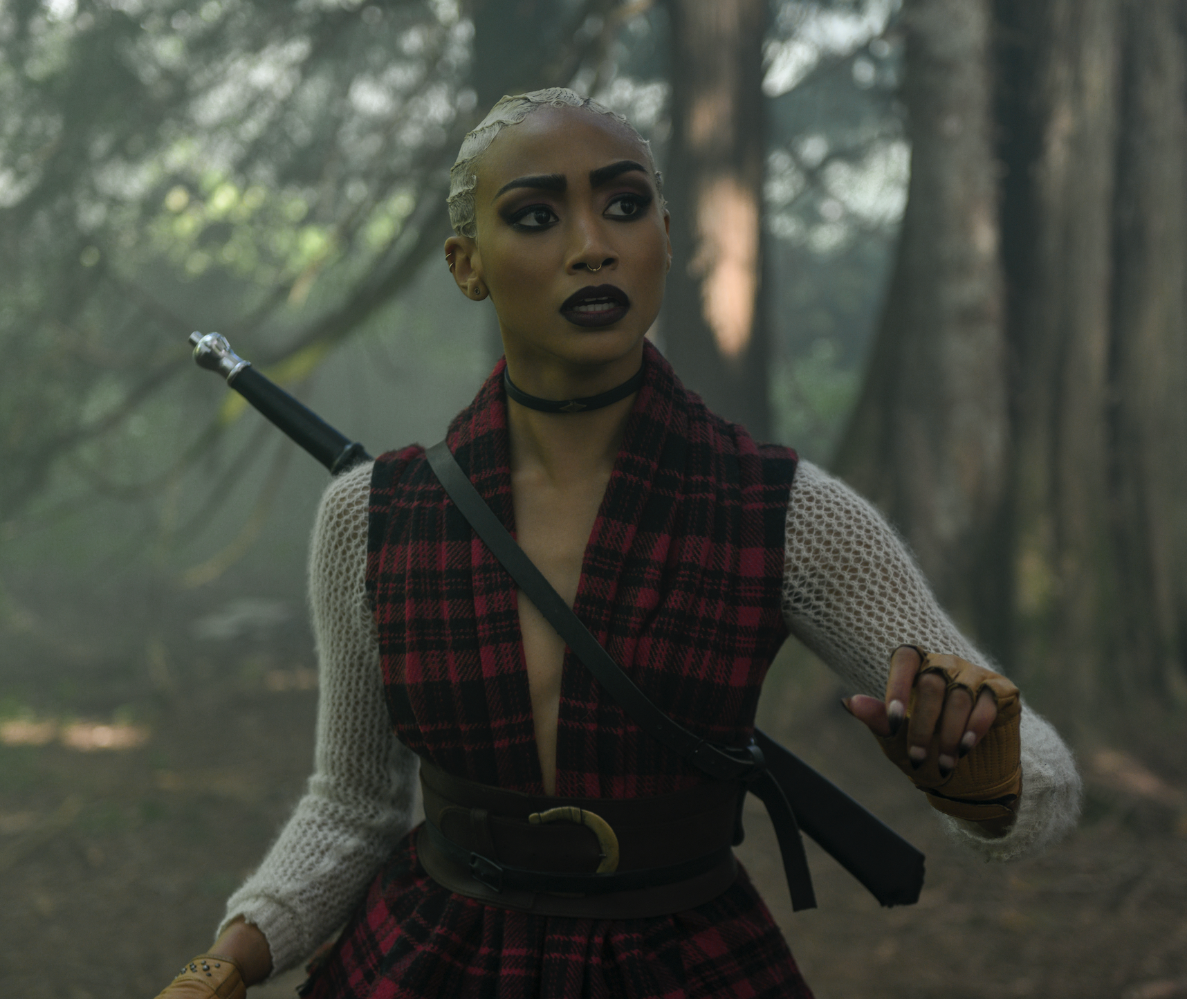 Prudence wearing a deep-neck plaid top with a thick belt around her waist and a leather choker