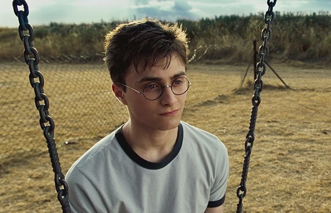Daniel Radcliffe as Harry Potter sits on a swing looking glum