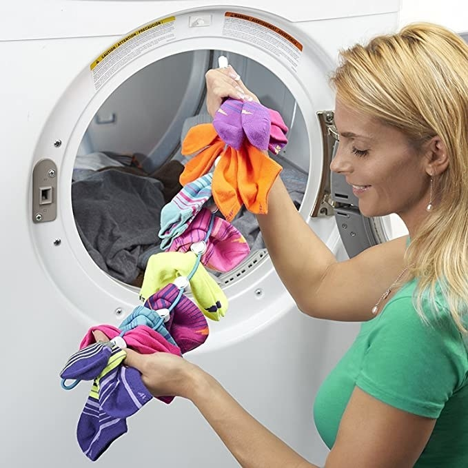 A woman putting the sock dock filled with socks into the washing machine.