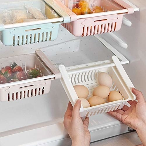 Some eggs and fruits organised neatly in the fridge with the organising trays.