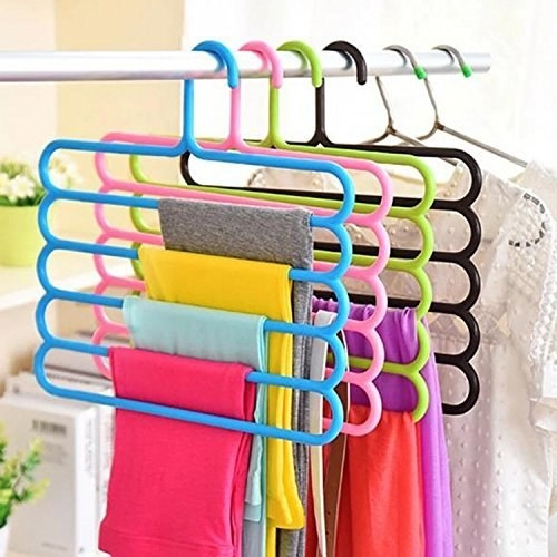 Clothes hanging off the hangers in a cupboard.