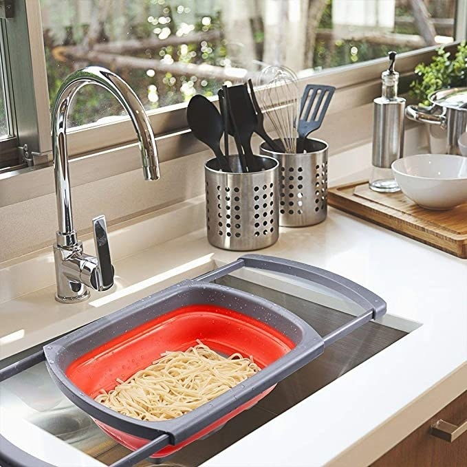 Some spaghetti being strained over the sink in the colander.