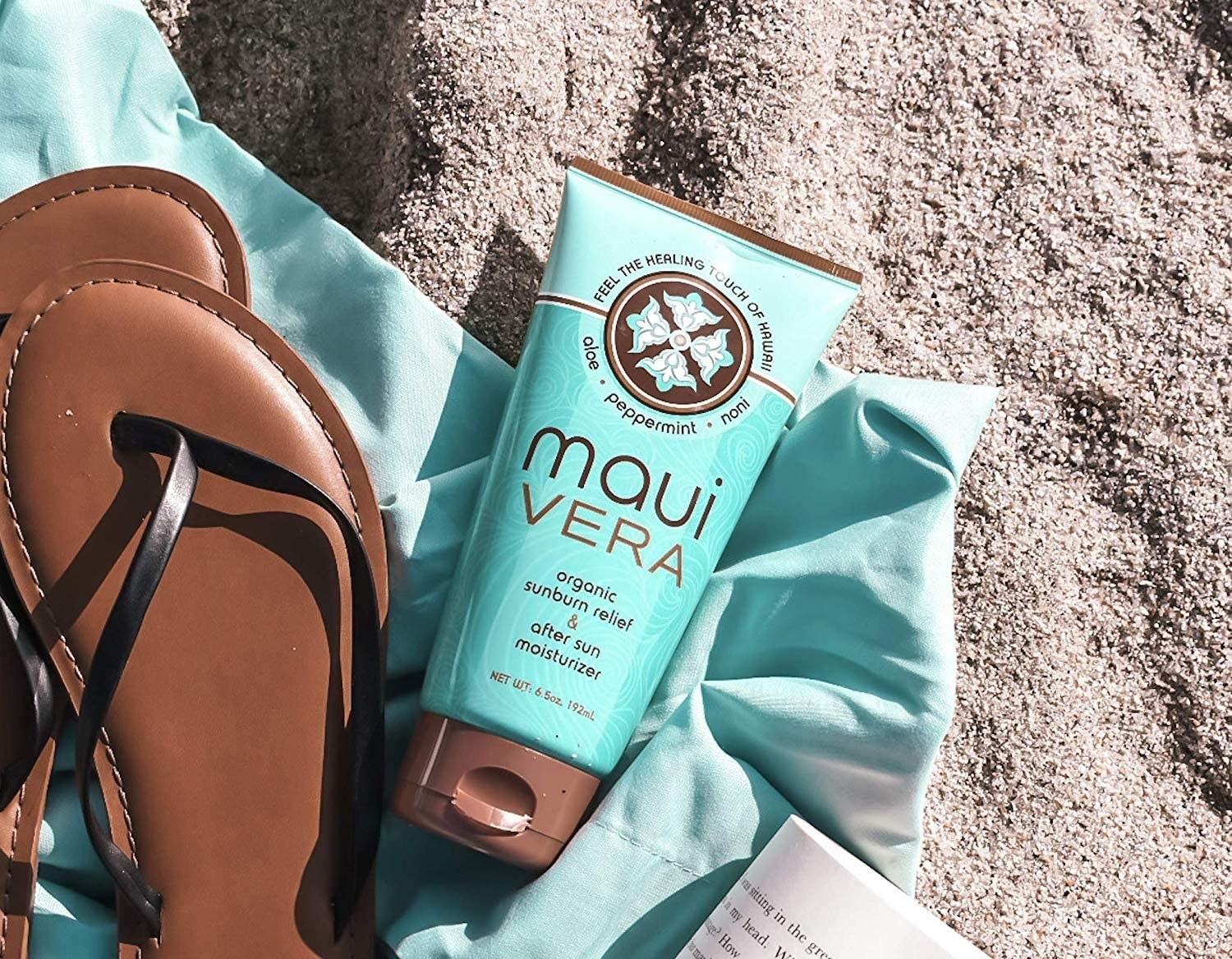 A tube of after sun moisturizer on a beach blanket next to flip flops