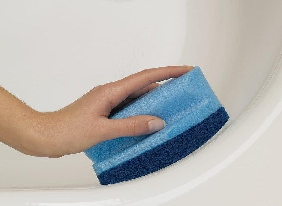 A person scrubbing the corner of a bathtub with the bathroom scrubber