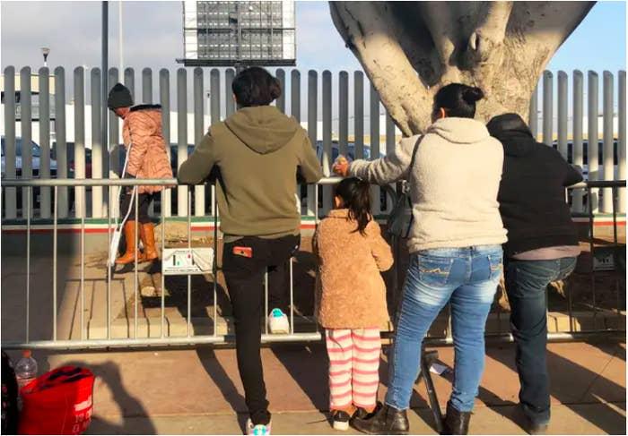 People seeking asylum in the US wait at the border crossing bridge in Tijuana, Mexico