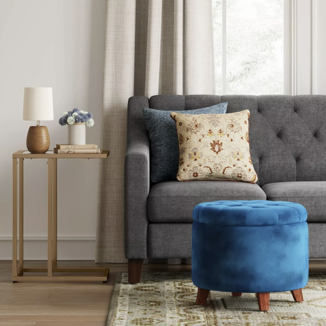 A round blue storage ottoman with a quilted top and brown wooden legs