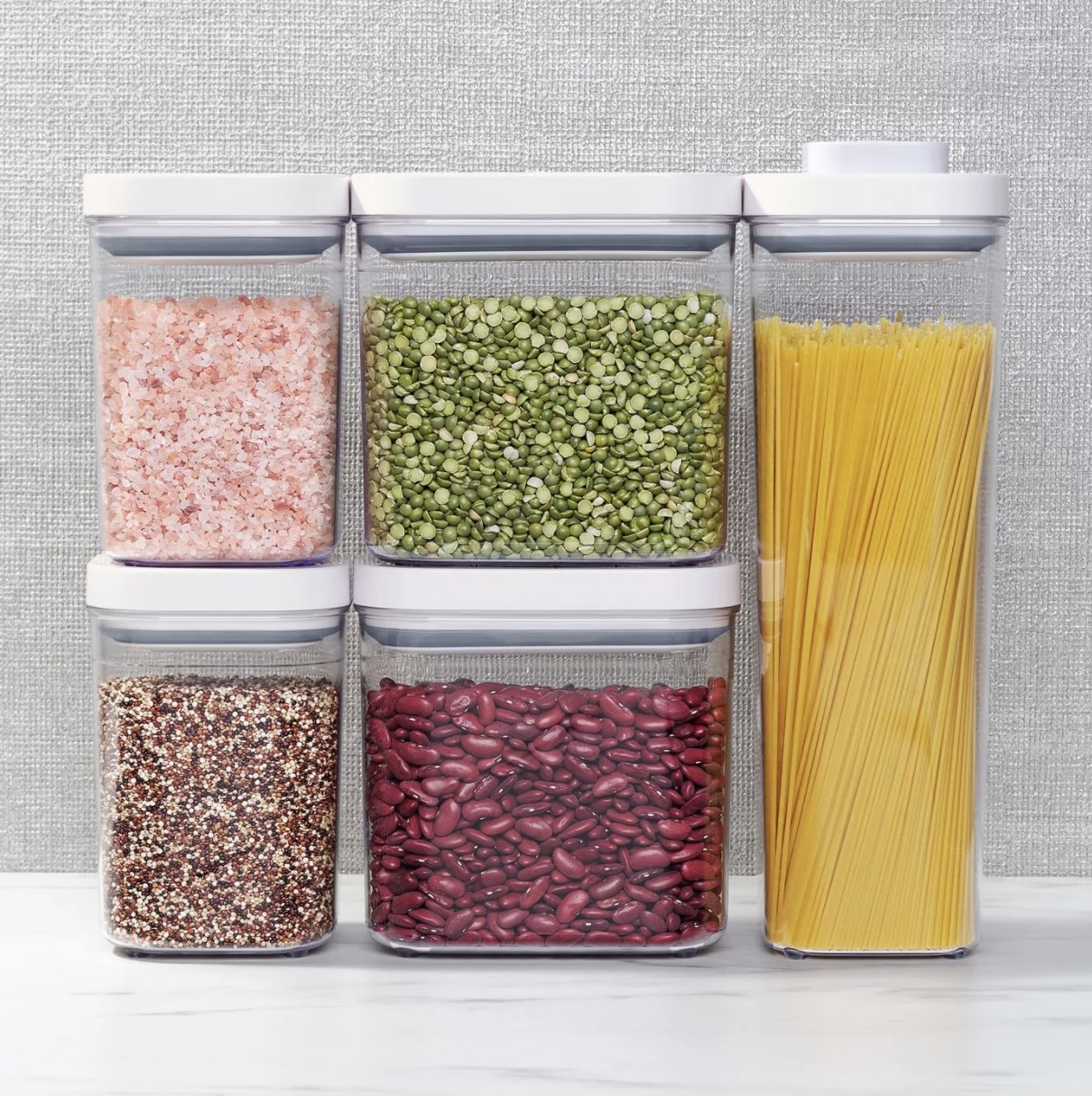 A set of five clear plastic containers with white tops holding various foodstuffs