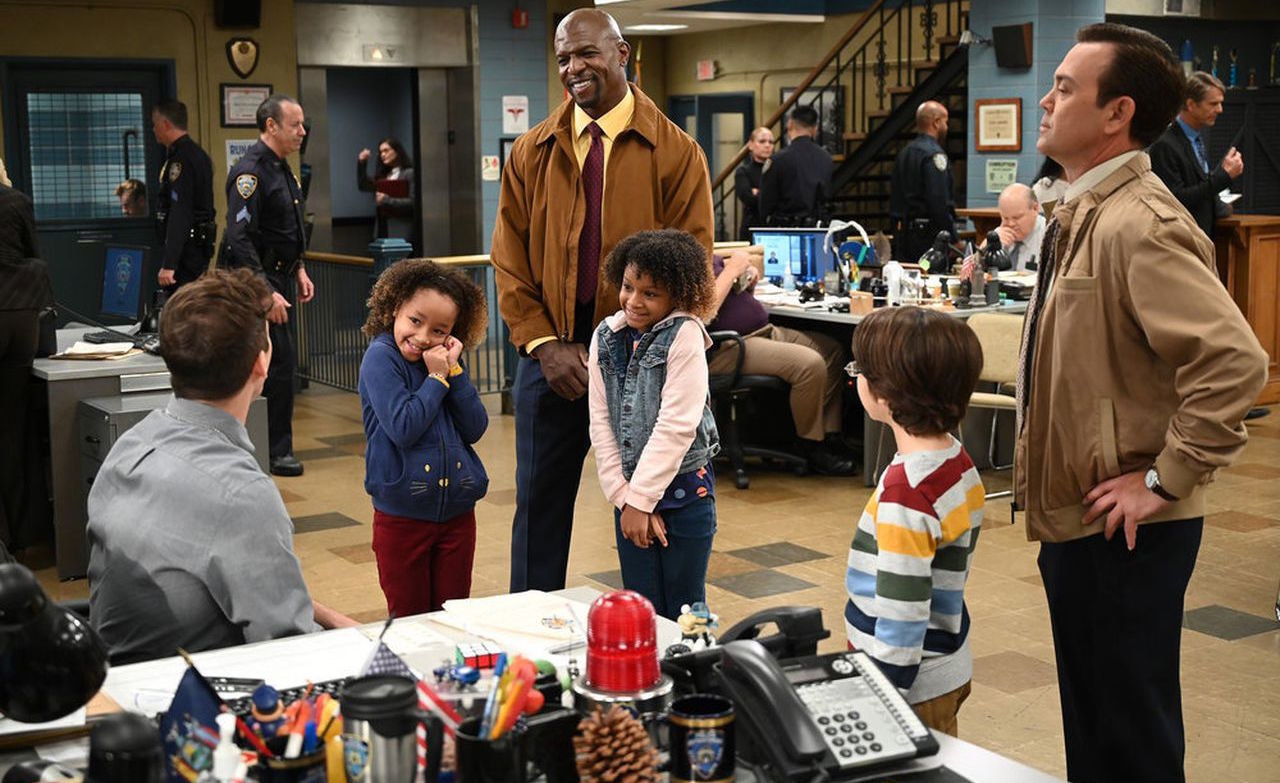 A still from Brooklyn 99 shows Jake, Terry, and Boyle with three children in their police precinct office area