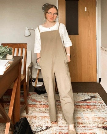 reviewer in tan linen overalls
