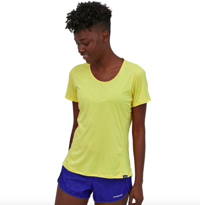 Model wears light yellow scoopneck tee with violet running shorts