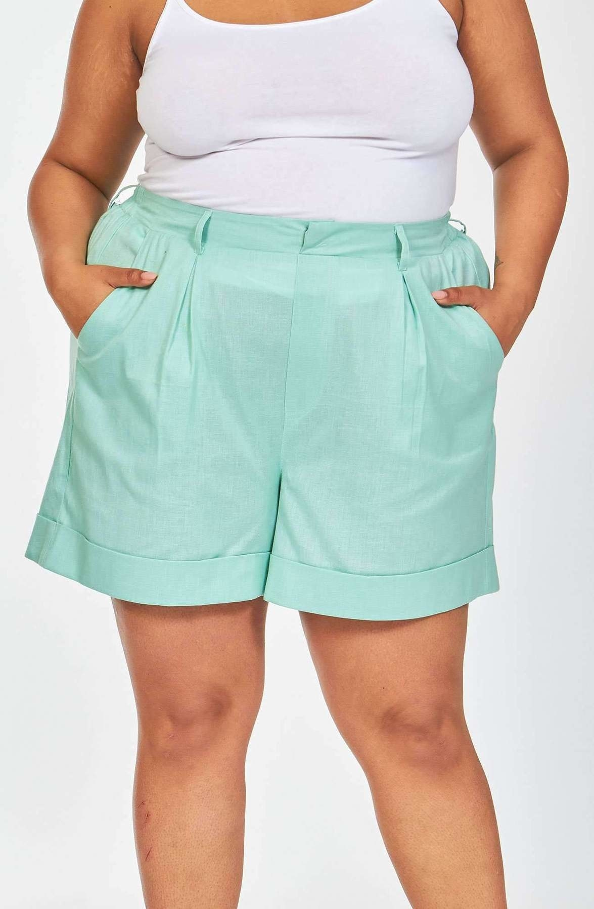 Model wearing shorts with folded hem, pleated front, and side pockets in teal.