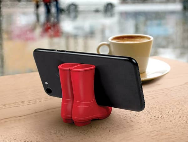the red rain boots holding a phone